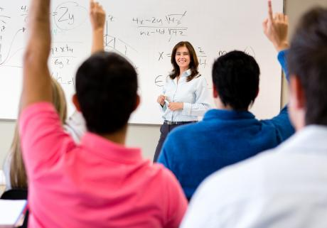 Students raising hands in a college classroom